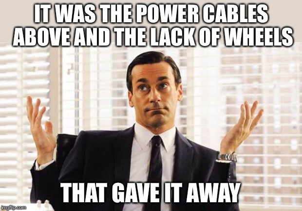 don draper | IT WAS THE POWER CABLES ABOVE AND THE LACK OF WHEELS THAT GAVE IT AWAY | image tagged in don draper | made w/ Imgflip meme maker