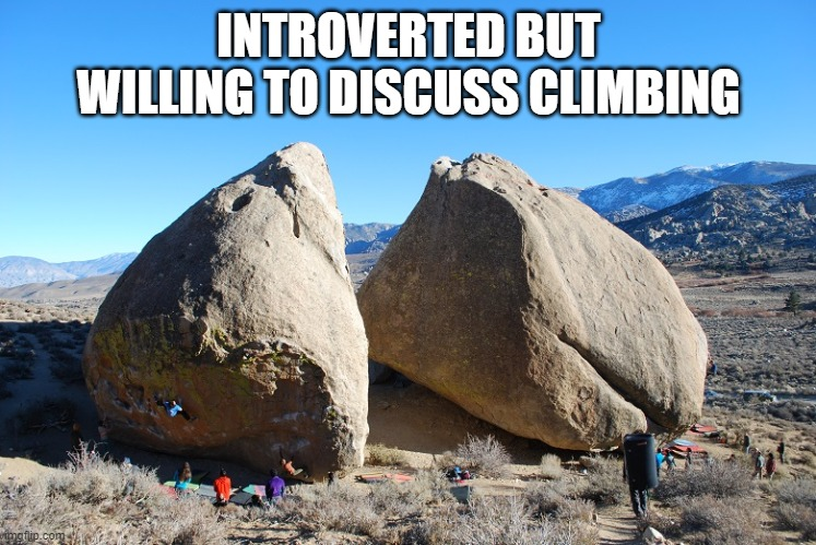 People standing around two large grey boulders